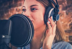 Female voiceover talent recording into microphone